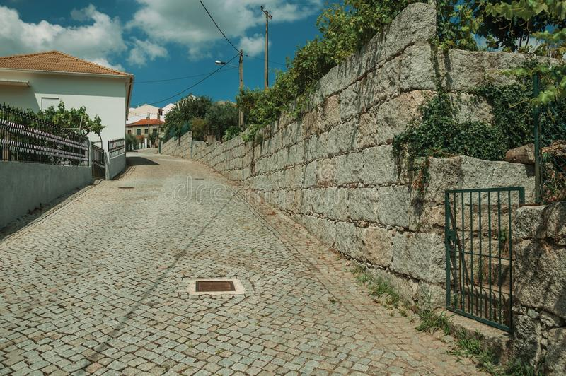 Rue sur une pente avec la porte de mur en pierre et de fer photo libre de droits