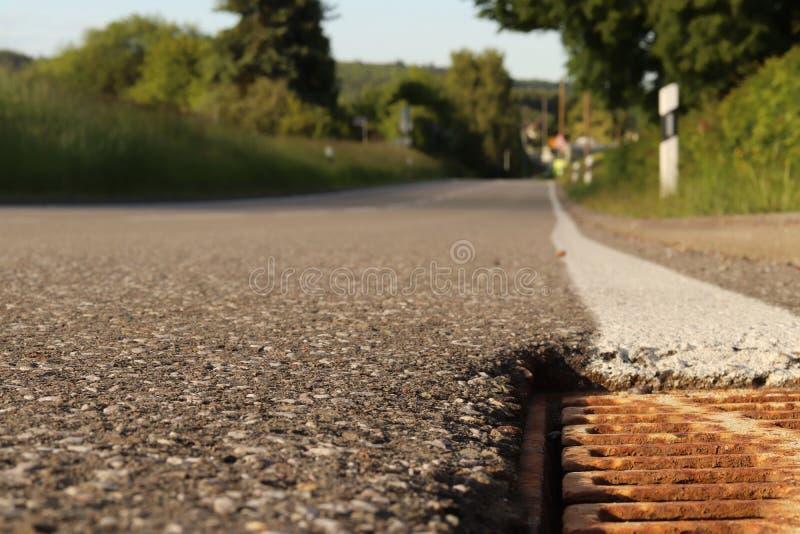 rue vide avec un caniveau dans l'avant image stock
