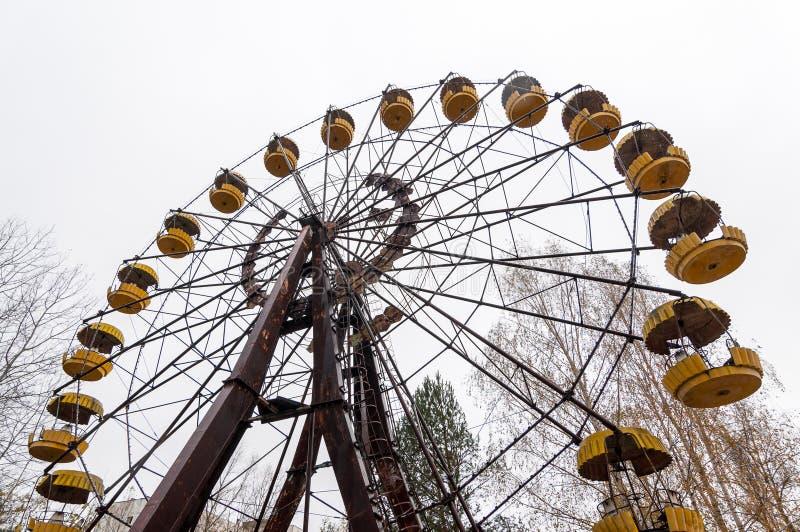 Rueda abandonada de la visión en pueblo fantasma de la ciudad del pripyat en la zona Chernóbil Ucrania del radioactiv de la exclu imagenes de archivo