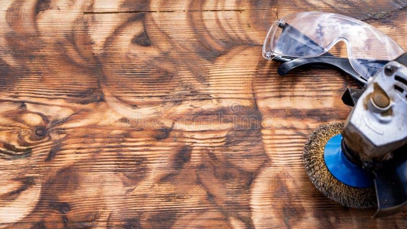 rueda abrasiva de la amoladora de madera y gafas de seguridad pulidas fondo imagenes de archivo