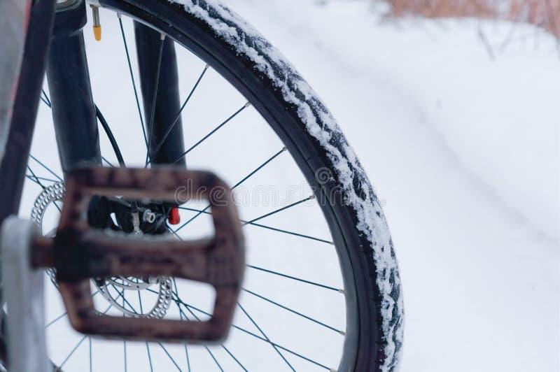 Rueda de bicicleta en fondo nevado del camino fotografía de archivo