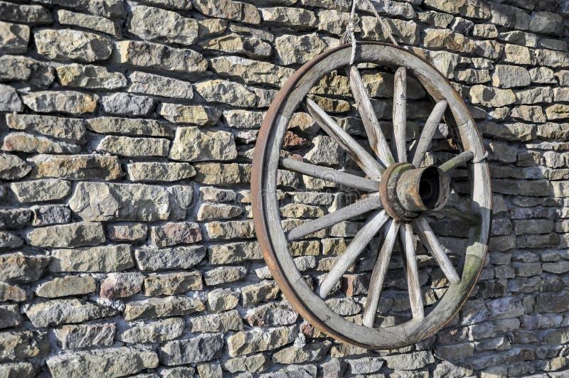 Rueda de carro rústica de madera vieja en una pared de piedra con el eje y los rayos imagenes de archivo