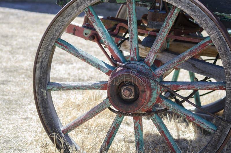 Rueda de carro vieja hundida en la tierra fotos de archivo