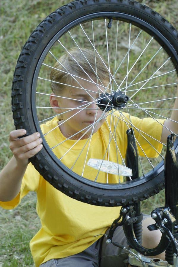 Rueda de la bici de la fijación del muchacho imagenes de archivo