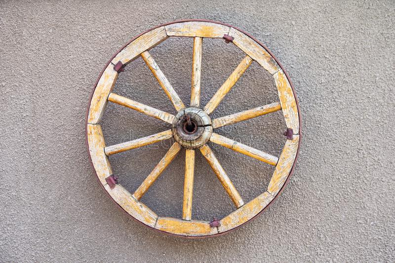 Rueda de madera vieja del caballo-carro en la pared imagen de archivo libre de regalías