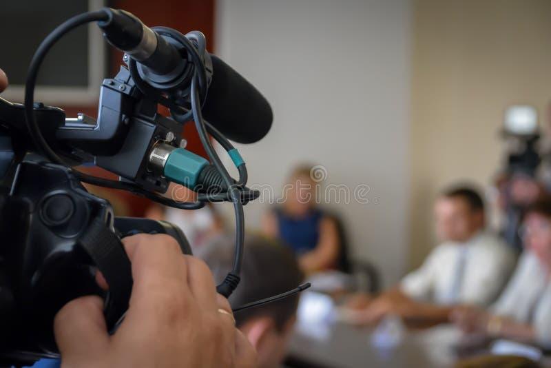 Rueda de prensa de la grabación de la cámara de televisión Portavoces en el escritorio Periodistas que cubren un evento de la pre foto de archivo