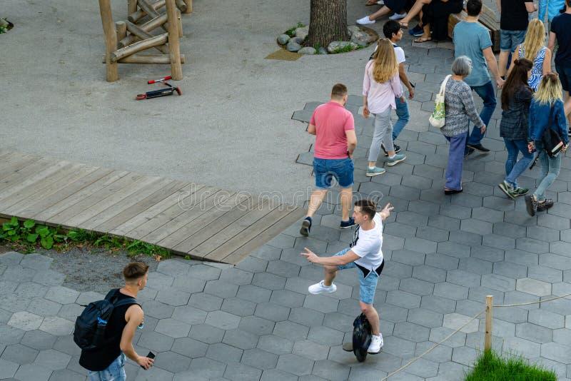 Rueda del montar a caballo del hombre joven mono en el parque de Zaryadye Zaryadye es nueva atracción turística de Moscú cerca de foto de archivo