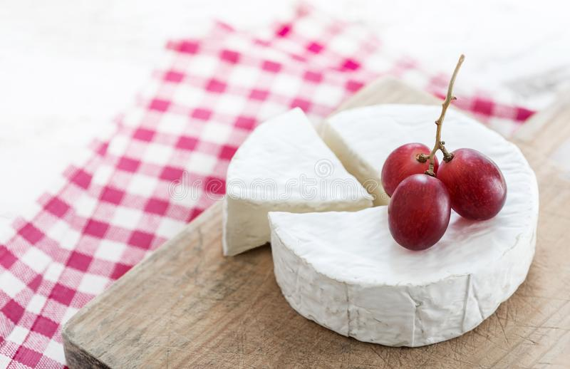 Rueda del queso suave con un pedazo de queso en un tablero de madera con foto de archivo libre de regalías