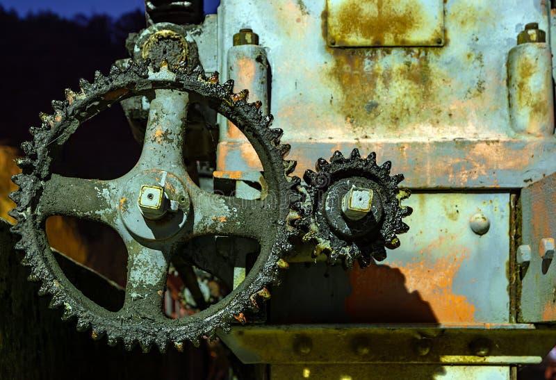 Rueda dentada aceitosa y oxidada del vintage en la noche foto de archivo