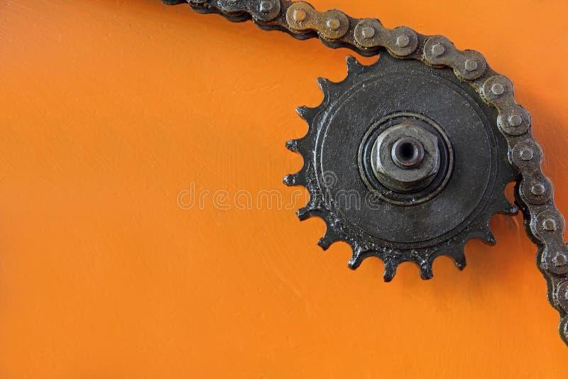 Rueda dentada del metal con la cadena en fondo anaranjado imagenes de archivo
