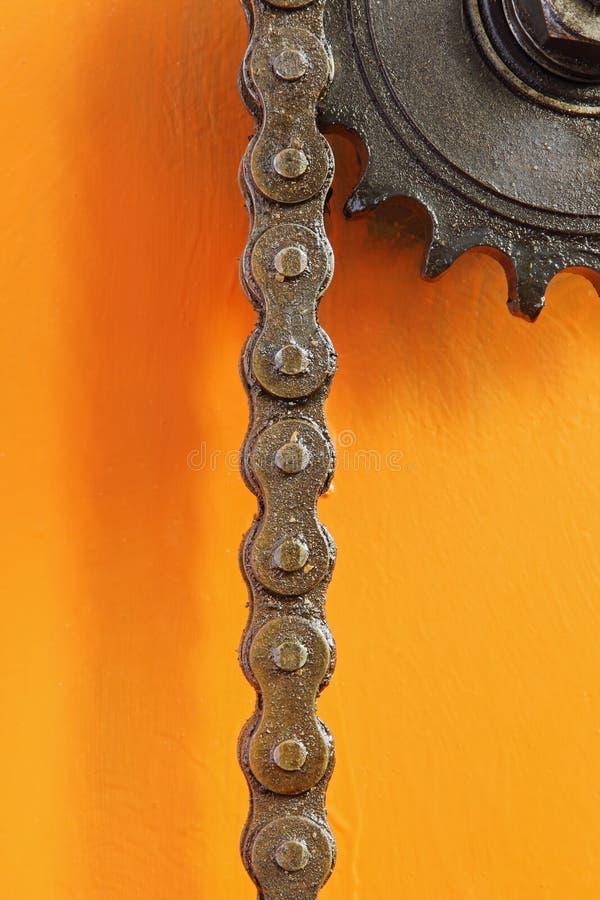 Rueda dentada y cadena negras del metal en fondo anaranjado fotografía de archivo libre de regalías