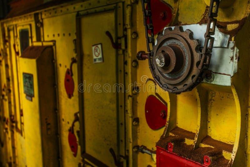 Rueda dentada y cadena oxidadas viejas en una maquinaria amarilla del secador usada adentro foto de archivo