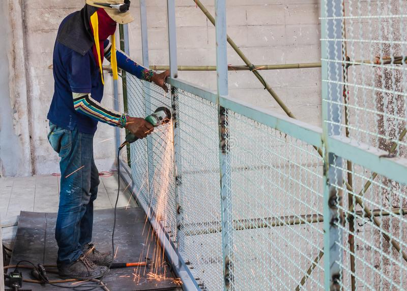 Rueda eléctrica del uso del hombre del trabajador que muele en malla de alambre de la estructura de acero fotografía de archivo libre de regalías