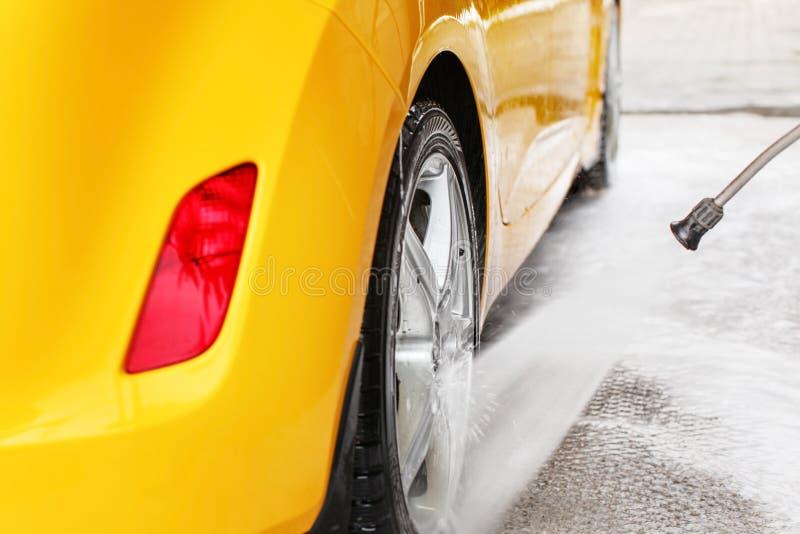 Rueda posterior del coche amarillo que es lavado con la corriente del agua del jet en c imagenes de archivo