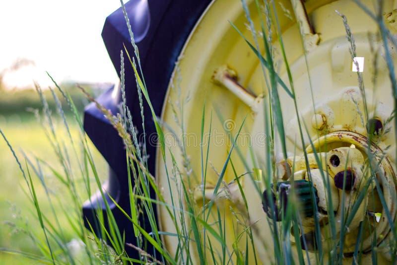 Rueda vieja del tractor detrás de las cuchillas de la hierba fotos de archivo