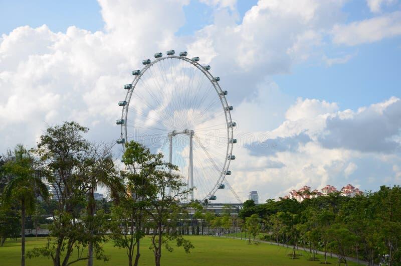 Rueda volante gigante delante del jardín hermoso fotografía de archivo libre de regalías