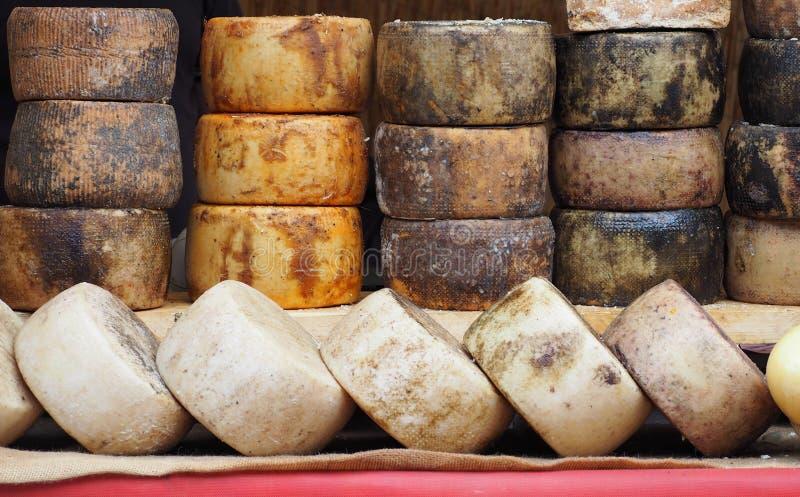 Ruedas del queso de Pecorino con diverso condimento dispuesto geométrico en la ventana de una tienda de alimentos fotografía de archivo