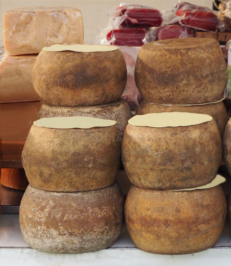 Ruedas del queso sazonado de Pecorino, especialidad sarda hecha con leche del ` s de las ovejas, en un mercado local fotos de archivo libres de regalías