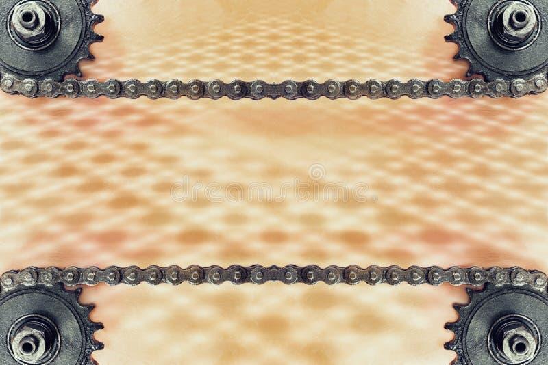 Ruedas dentadas y cadena doble en fondo del grunge con el modelo geométrico foto de archivo