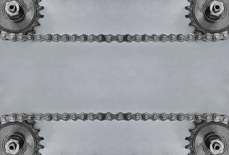 Ruedas dentadas y cadena doble en fondo gris con el espacio vacío imagenes de archivo