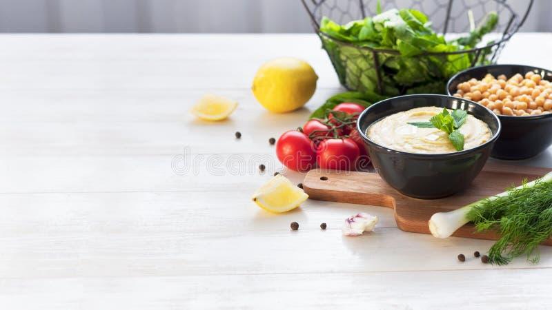 Ruede con hummus, los garbanzos, el limón, los tomates de cereza y las hierbas en un fondo de madera rústico blanco Cocina de Ori fotografía de archivo