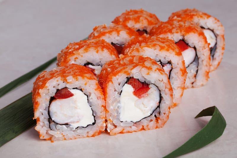 Ruede con la naranja del tobiko, el camarón y las pimientas rojas dulces en un menú tropical del primer de la hoja aislado fotos de archivo libres de regalías