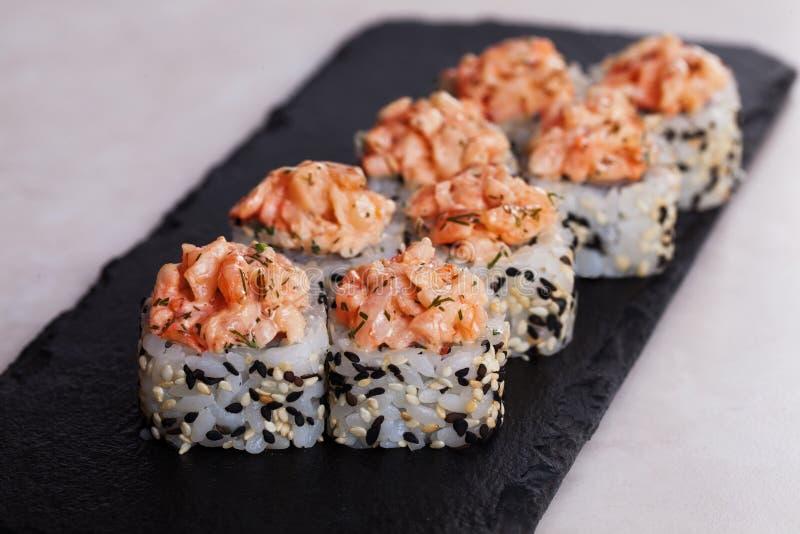 Ruede con la placa negra de la ensalada del camarón en sésamo del arroz imagen de archivo