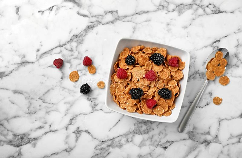Ruede con los copos de maíz y las bayas en la opinión de sobremesa de mármol Cereal entero del grano para el desayuno imagen de archivo libre de regalías