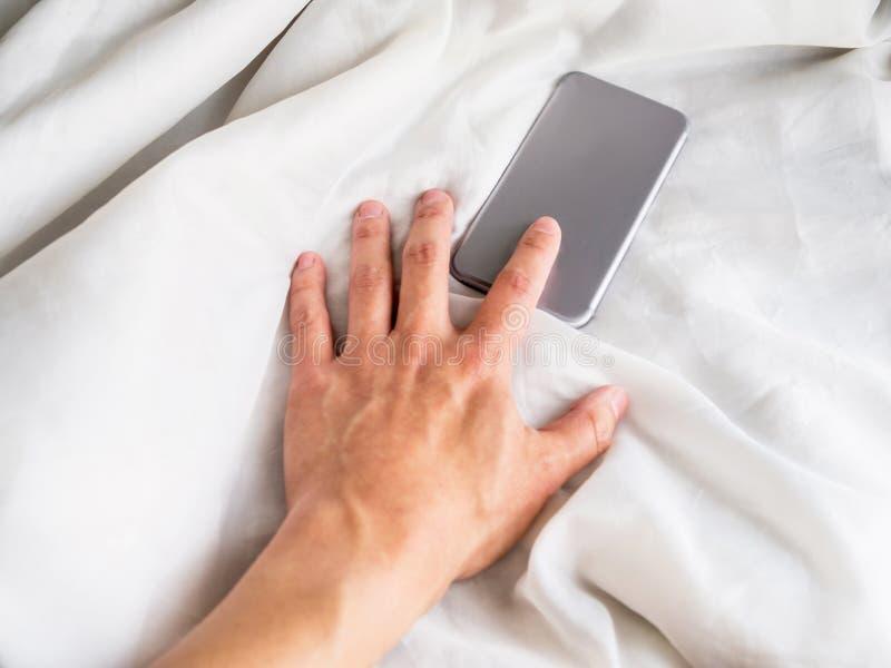 Rufen Sie auf dem Bett mit der Hand an, die auf Daunendecke erreicht stockfotos