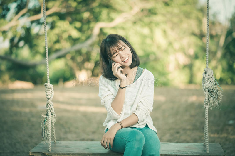 Rufen Sie Frau bei der Unterhaltung im intelligenten Telefon im Park an stockbild