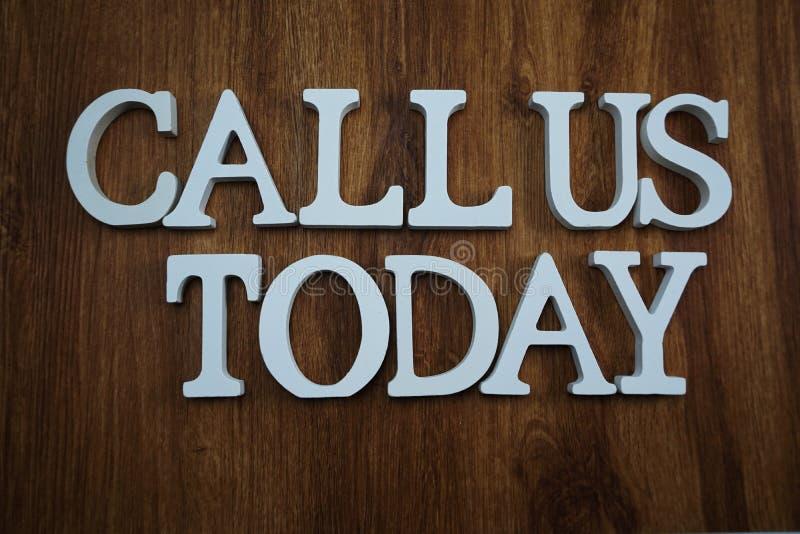 Rufen Sie uns heute Alphabetbuchstaben Draufsicht über hölzernen Hintergrund an lizenzfreies stockbild