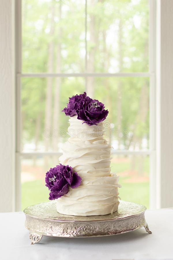 Rufsa bröllopstårtan med ätliga purpurfärgade Sugar Flowers royaltyfri bild