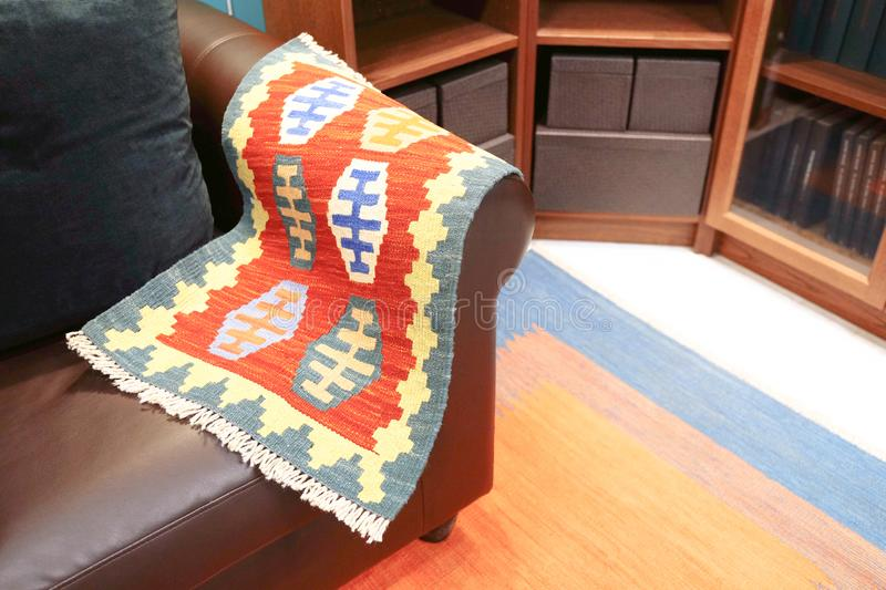 Rug on the leather chair. Colorful traditional Peruvian style, end-up surface stock photos