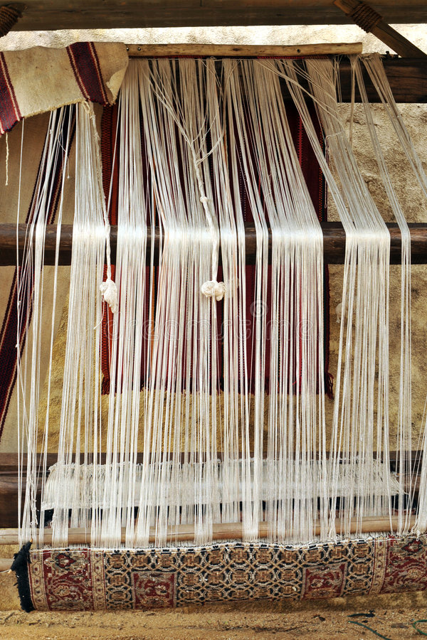 Rug Loom. A replica of an ancient rug loom with an Oriental rug partially complete royalty free stock image