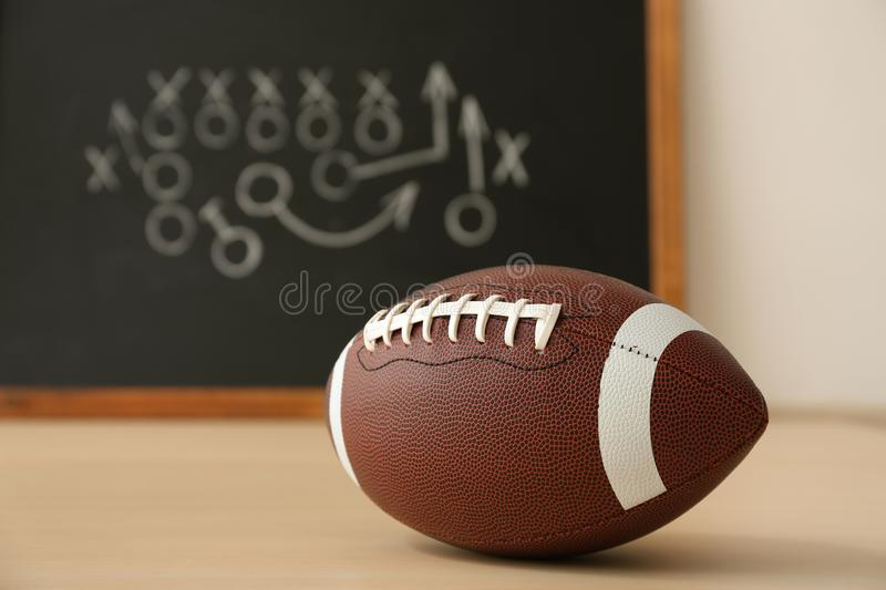 Rugby ball near chalkboard with football game scheme. On table. Space for text stock image