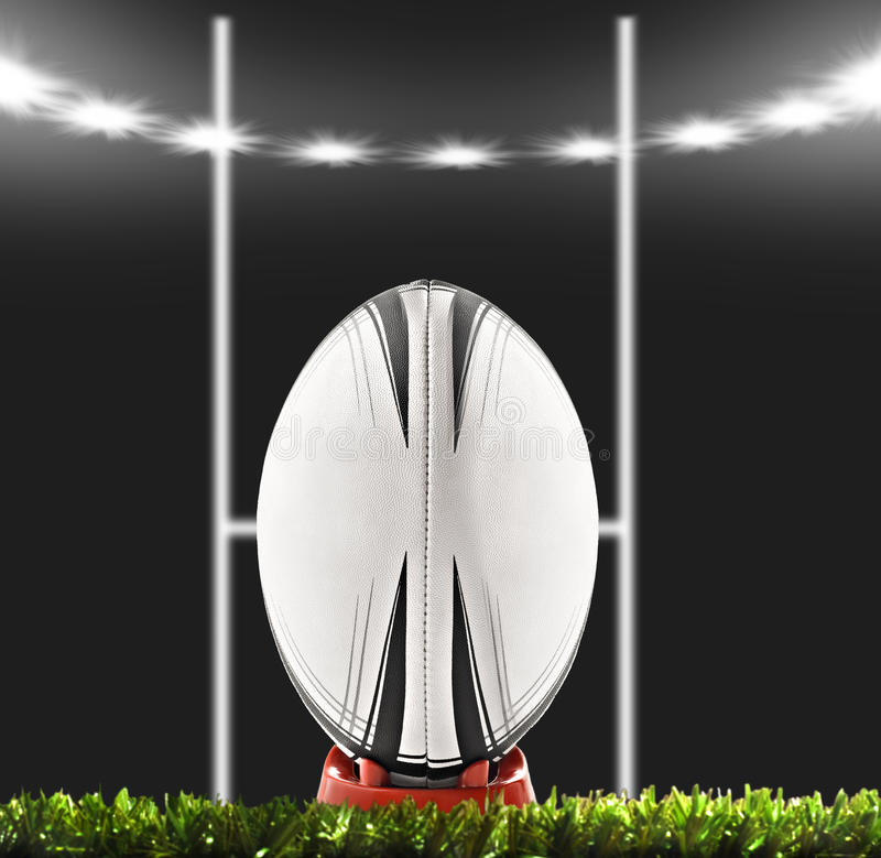 A rugby ball on a rugby field. With goal posts and lights of stadium stock photos