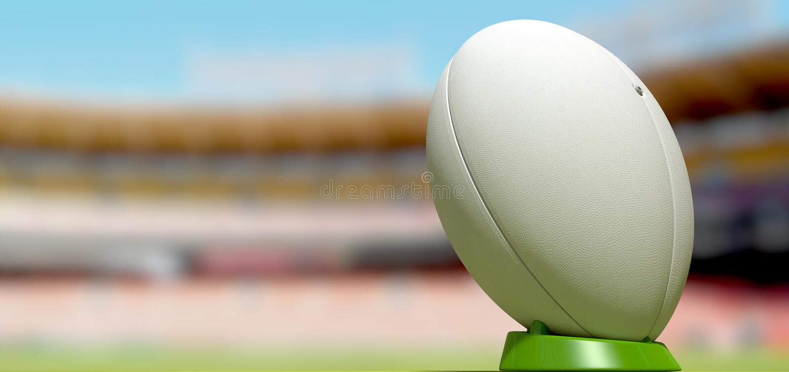 Rugby Ball In A Stadium Daytime. A plain white textured rugby ball on a green kicking tee in a stadium stock photography