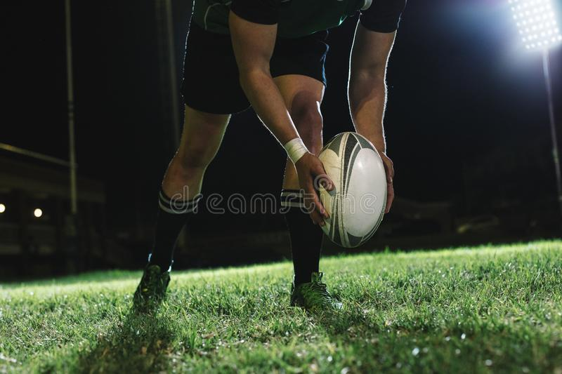 Rugby player kicking field goals. Rugby player dropping the ball to the ground for kicking as it touches the ground stock photos