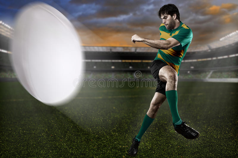 Rugby player. In a green and gold uniform on a stadium royalty free stock images