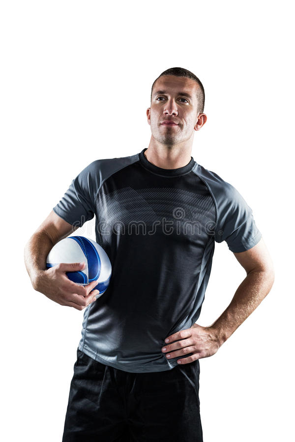 Rugby player holding ball with hand on hip. Against white background royalty free stock image
