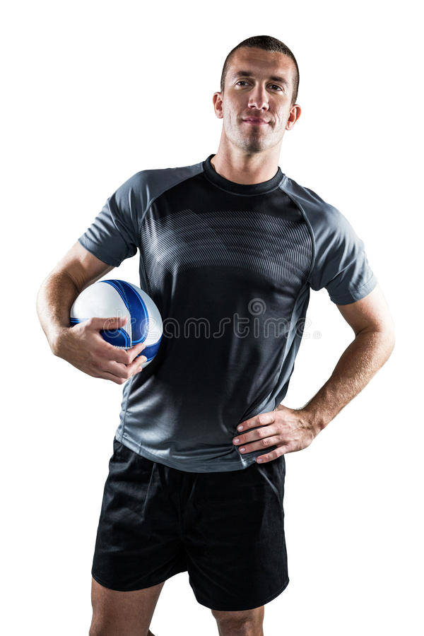 Rugby player holding ball with hand on hip. Portrait on rugby player holding ball with hand on hip against white background royalty free stock photo