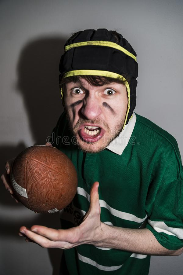 Rugby player holding ball in hand and making faces royalty free stock image