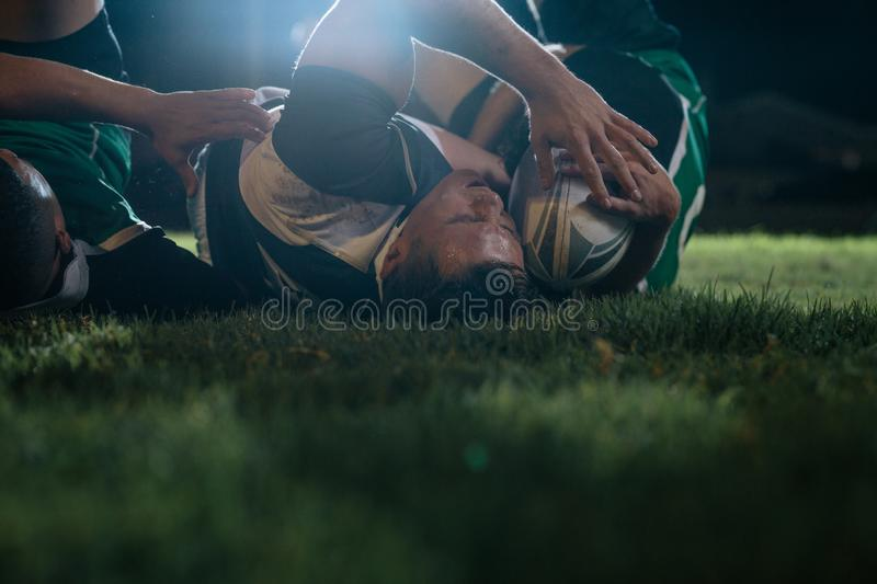 Rugby players fighting for ball at stadium royalty free stock image
