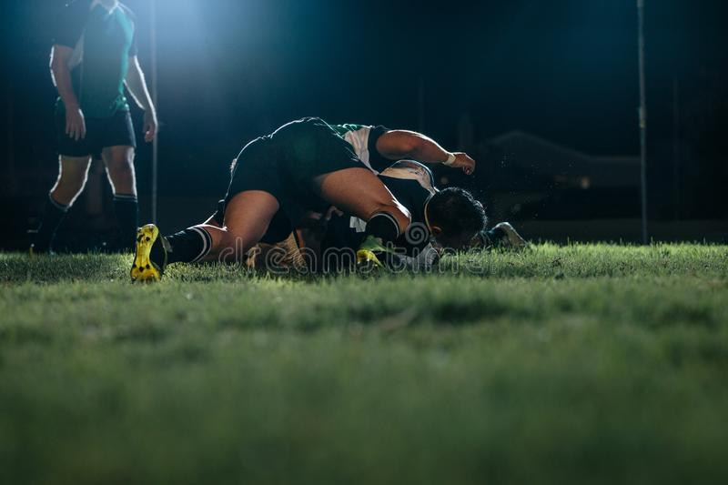 Rugby players striving for ball on sports arena. Strong rugby players fighting for ball during game at stadium. Rugby team striving for ball in night game on stock image