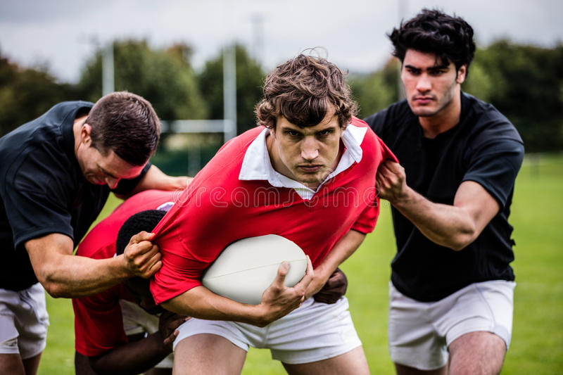 Rugby players tackling during game stock images