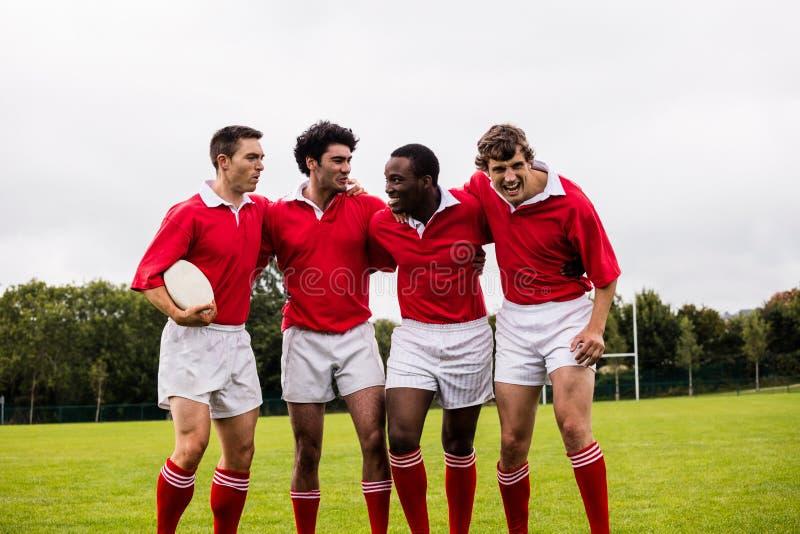 Rugbyspelers die met rond wapens glimlachen stock afbeelding