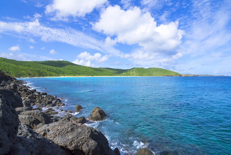 Rugged Caribbean coastline and rolling green hills. Rugged dark boulders contrast wide sandy beach and rolling green hills of Resaca Beach on the Caribbean stock image