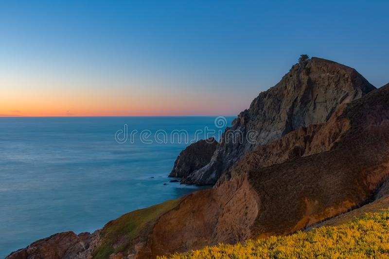 Rugged coastal cliffs by the Devil`s Slide trail in California at sunset and silky ocean from long exposure stock photo