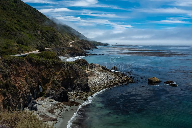 The rugged coastline of Big Sur, CA with the highway weaving and hugging the hills overlooking the ocean. Beautiful blue sky royalty free stock photos