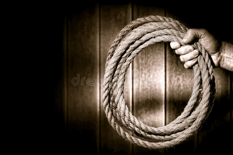 Rugged Cowboy Hand Firmly Holding a Ranching Rope. Rugged rancher cowboy hand firmly holding a ranching rope in a loop in an old rustic barn with dramatic light stock image